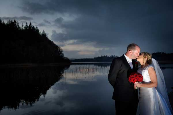 Real Wedding Kilronan Castle Bride and groom at dusk by lake